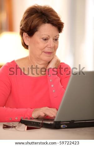 Closeup of senior woman at home with laptop computer - stock photo