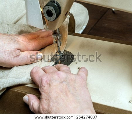 Closeup of senior woman's hands sawing linen border with sewing machine - stock photo