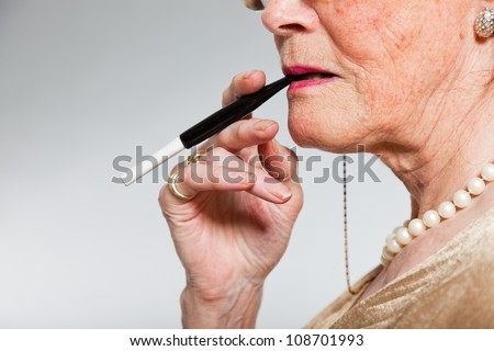 Closeup of senior woman smoking a cigarette. Studio shot on grey background. - stock photo