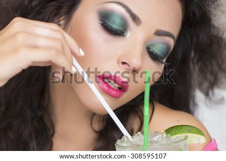 Closeup of sensual pretty brunette woman with curly hair and bright makeup with alcoholic mojito cocktail from mint soda light rum ice cubes and lime with straw, horizontal picture - stock photo