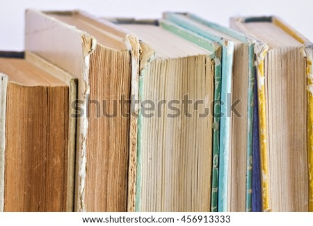 Closeup of several old books vertically placed on the shelf - stock photo