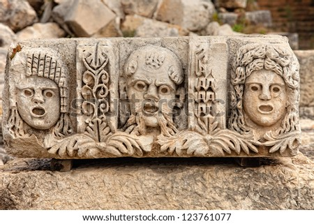 Closeup of several stone masks at an ancient theater in Myra Turkey - stock photo