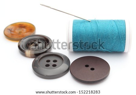 Closeup of sewing buttons and spool of thread with needle. Isolated on white background - stock photo