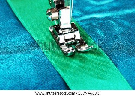 Closeup of sewing machine working part with  blue cloth - stock photo