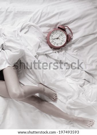 Closeup of sexy female legs with alarm clock on the bed. Woman lazy girl relaxing lazing in bedroom. - stock photo