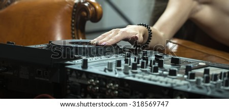 Closeup of sexy young naked dj woman lying on brown leather royal sofa at table with mixer console touching equipment by hand in night club indoor, horizontal picture - stock photo