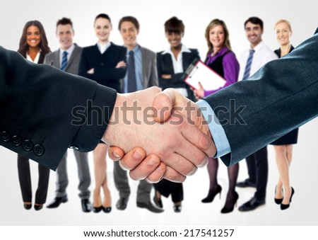 Closeup of shaking hands and business team in background - stock photo