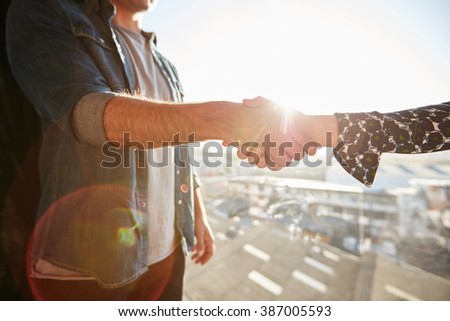Closeup of shaking hands of man and woman with lens flare. Focus on handshake on a sunny day. - stock photo