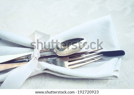 Closeup of Silverware tied in satin ribbon and a cloth napkin on cream white damask tablecloth from above.  Horizontal, vintage instagram  - stock photo
