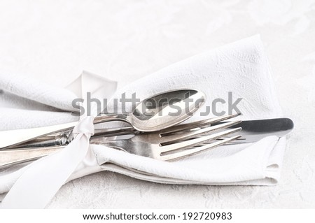 Closeup of Silverware tied in satin ribbon and a cloth napkin on cream white damask tablecloth from above.  Horizontal - stock photo