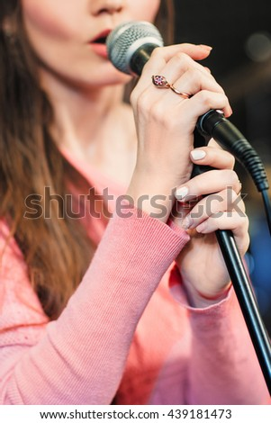 Closeup of singing caucasian woman. Young unrecognizable woman emotionally sings into the microphone, holding it with two hands. - stock photo