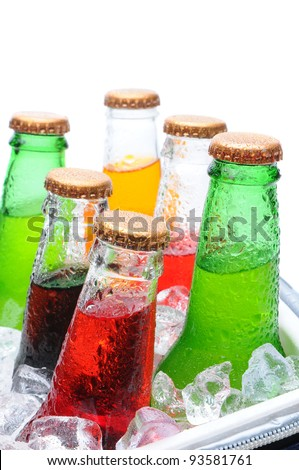 Closeup of six assorted soda bottles in an ice cooler with condensation. Vertical format over white with shallow depth of field. - stock photo