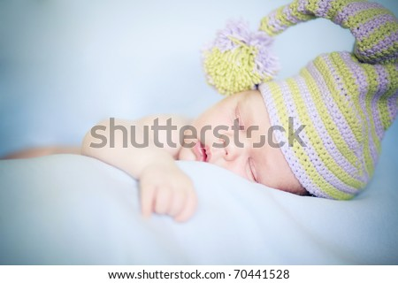 Closeup of sleeping baby in cap lying on blanket with hands in a comfortable position - stock photo