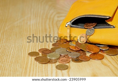 closeup of small change falling out of purse - stock photo