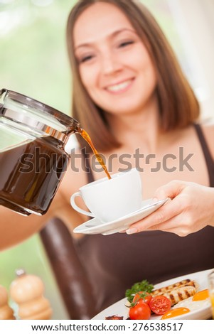 Closeup of smiling brunette woman pouring a cup of coffee - stock photo