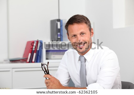 Closeup of smiling businessman in the office - stock photo