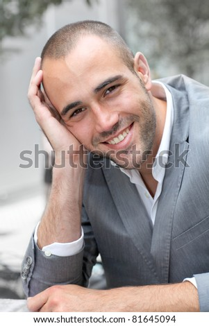 Closeup of smiling businessman in town - stock photo
