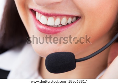 Closeup of smiling female customer service representative with microphone - stock photo