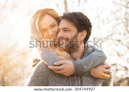 Closeup of smiling man carrying woman piggyback outdoor