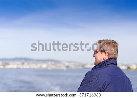 Closeup of smiling mature man looking away with fjord in background - stock photo