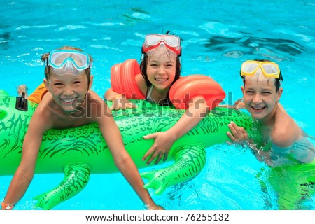 Closeup of smiling young brothers and sister in swimming pool with inflatable toy. - stock photo