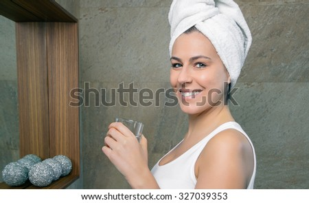 Closeup of smiling young woman with a towel over hair holding a glass of clean water in the bathroom. Health and beauty concept. - stock photo