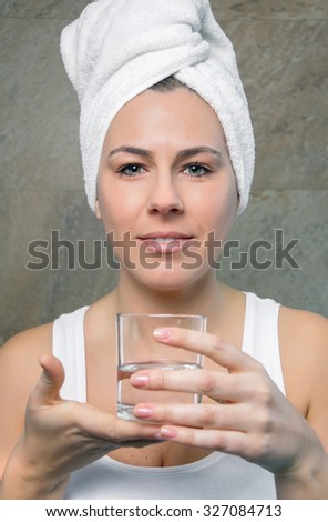Closeup of smiling young woman with a towel over hair holding a glass of clean water over a tiled wall background. Health and beauty concept. - stock photo