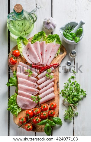 Closeup of smoked cold cuts with pepper and herbs - stock photo