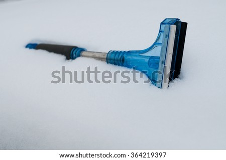 Closeup of snow and ice car cleaner in the snow - stock photo