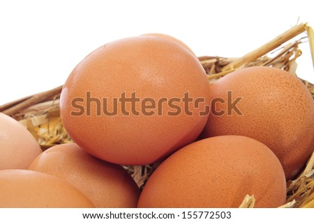 closeup of some brown eggs in a basket with straw on a white background - stock photo