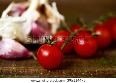 closeup of some cherry tomatoes and some garlic cloves on a rustic wooden table - stock photo