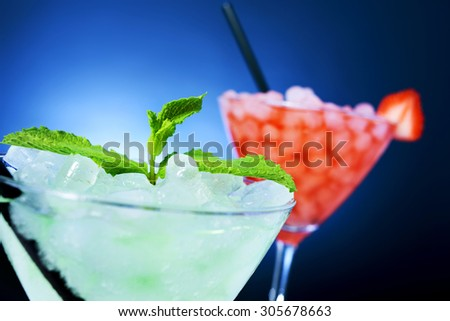 closeup of some cocktail glasses with beverages of different colors garnished with mint leaves and a strawberry over a blue lighted background - stock photo