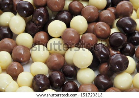 closeup of some different ball-shaped chocolates made with black chocolate, white chocolate and milk chocolate - stock photo