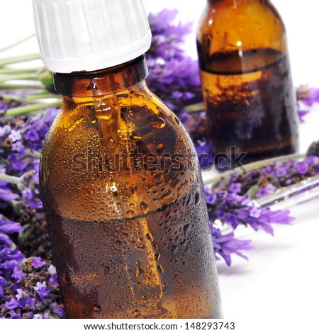 closeup of some dropper bottles with natural remedies and a pile of lavender flowers on a white background - stock photo