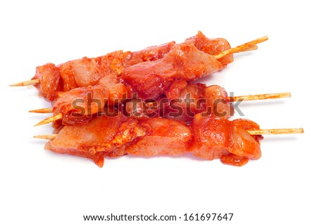 closeup of some raw spiced chicken meat skewers, on a white background - stock photo