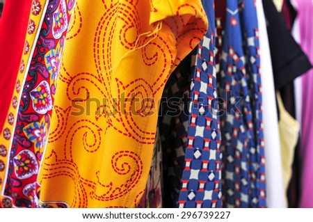 closeup of some used clothes hanging on a rack in a flea market - stock photo