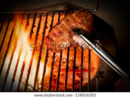 Closeup of someone turning a tasty steak cooking on a fire - stock photo