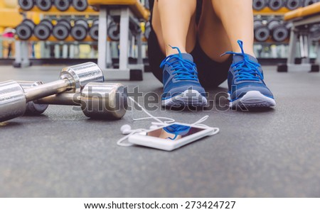 Closeup of sporty man sitting on the floor of fitness center with dumbbells and smartphone with earphones in the foreground - stock photo