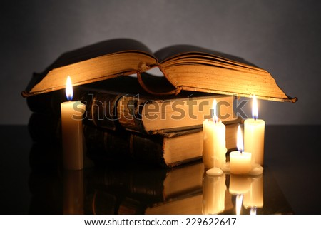 Closeup of stack of old books near lighting candles on dark background - stock photo