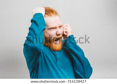 Closeup of stressed businessman holding a mobile phone and screams into it. - stock photo