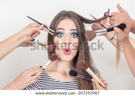 closeup of surprised beautiful blond girl getting makeup done by many people isolated - stock photo