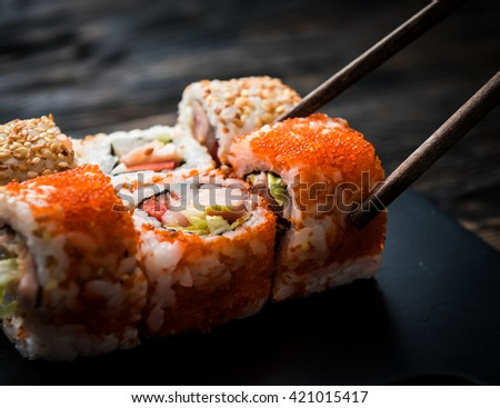 closeup of sushi rolls with chopsticks on dark background - stock photo