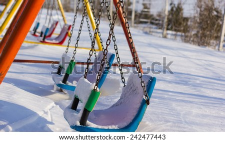Closeup of swings in a children play area after snowfall - stock photo