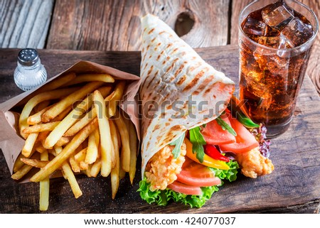 Closeup of tasty kebab with fries and cod drink - stock photo