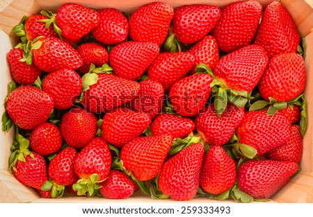 Closeup of tasty spanish strawberries freshly collected on a wooden box view from above - stock photo
