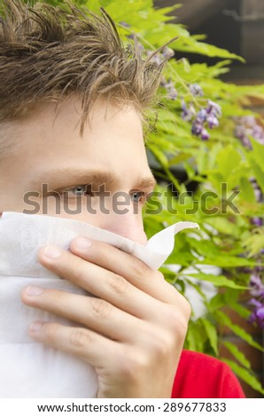 Closeup of teenage boy having allergic reaction, selective focus on his eyes. Shallow depth of field - stock photo