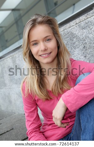 Closeup of teenage girl sitting on a school bench - stock photo