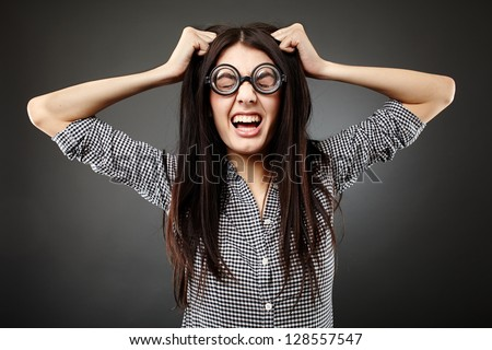 Closeup of teenage nerd shouting angry pulling her hair over gray background - stock photo