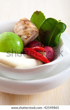 Closeup of Thai ingredients, galangal, lime, lemongrass, chili, shallots and lime leaves - stock photo