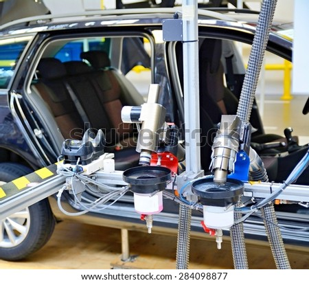Closeup of the automated machine at assembly line in car factory. - stock photo